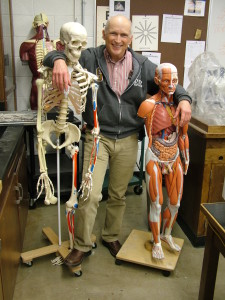 Dr. Paul Gardner gets all buddy-buddy with his anatomy models to show his excitement for having a new female cadaver on campus. Photo by Shay Duncan