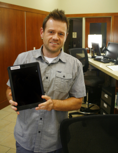 Zach Allred shows off one of the new iPads Snow College recently bought. They're  available for checkout at the library. Photo by Tyler Aldous.