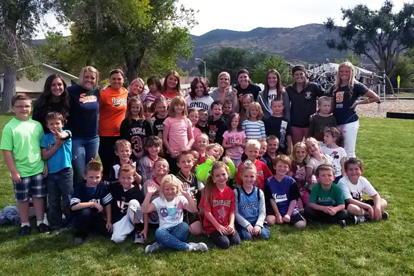 The Snow College softball team pose with a group of Manti Elementary School students.  The players volunteered as teacher aides on Tuesdays this fall as part of the AmeriCorps program at the school.  Photo by Mallory Wilkinson