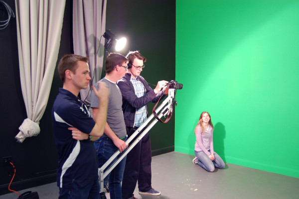 Sarah Stratford poses in front of a green screen, while Taylor Yorgason, Parker Kelly, and Nick Nuttall situate the camera during their video class offered here at Snow. Photo by Hannah Branch