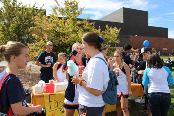 Snow cheerleaders help put temporary tattoos on students' cheeks at the tailgate party.  Photo by Brynnlee Nelson.