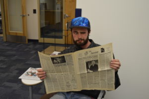 Adam Allred takes a look over one of the old Snowdrift newspapers, taking notice to how much has changed compared to today. Photo by April Carver